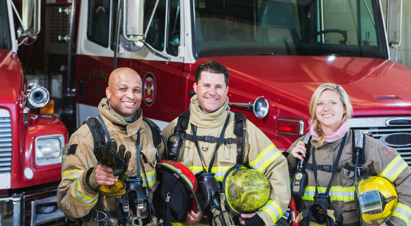 Three firefighters smiling in front of fire truck